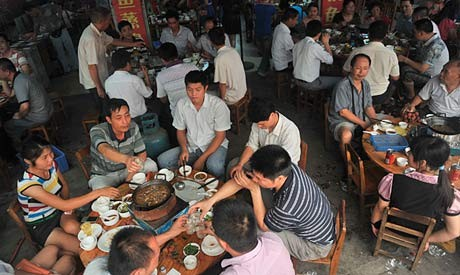Photo of a restaurant at dinner time with dog hot pot in a restaurant in Yulin, Guangxi province.